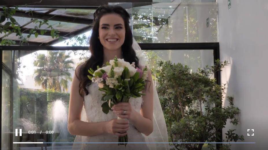 身穿白色婚纱的年轻黑发新娘捧着她的花束开心地散步